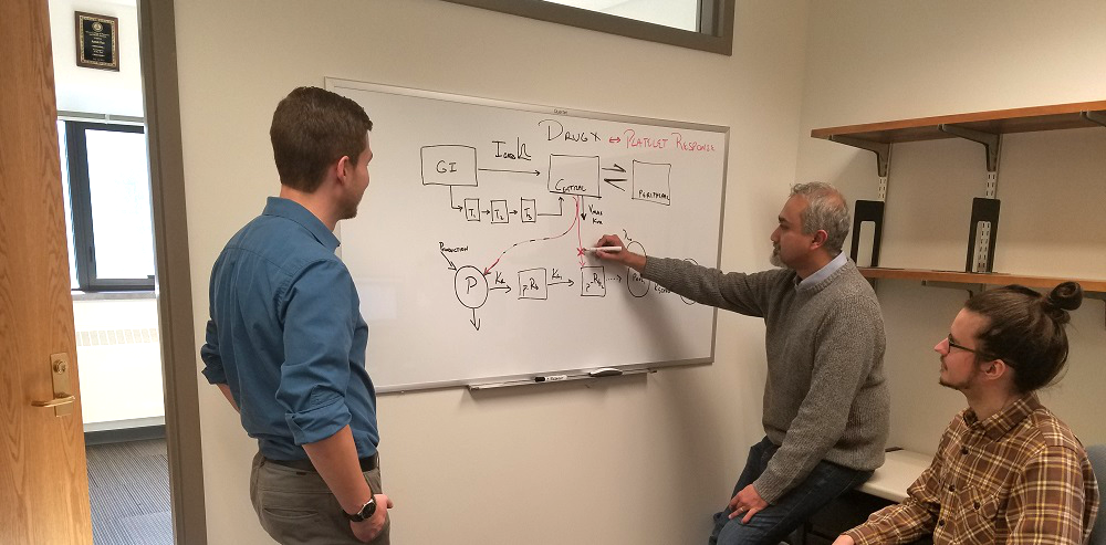 Pai lab team members at white board